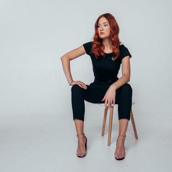 Sitzende Frau mit schwarzem Outfit